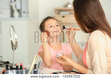 Young woman and her little daughter applying makeup at home