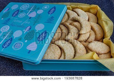 Homemade half-moon shaped cookies in a tin box