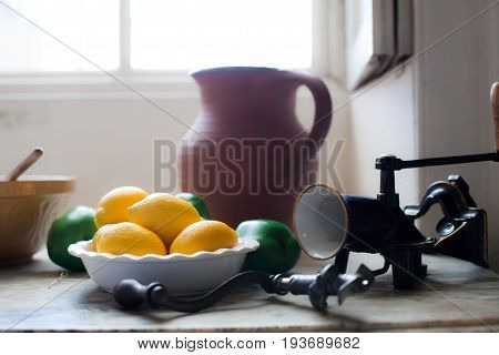Cottage kitchen. Lemons on a vintage English country kitchen table. Retro Victorian farmhouse image with selective focus on bowl of lemons.