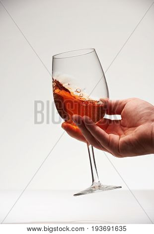 Tasting red wine close-up isolated on white background. Hand shake red wine in glass