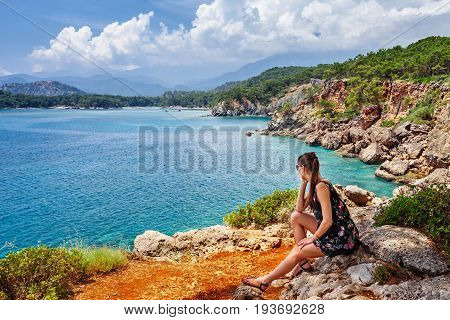 Portrait Of Beautiful Tanned Woman Sitting At The Sea Coast. Hot Summer Day And Bright Sunny Light.