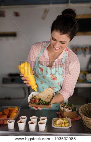 Smiling waitress preparing meal for customer