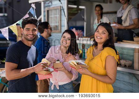 Portrait of friends standing with snacks in food truck van
