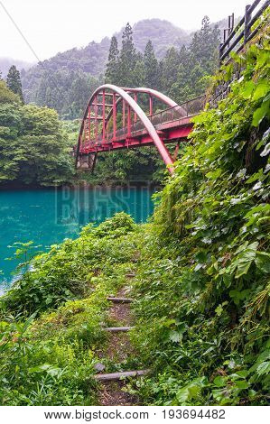 Landscape With View Of Red Arch Bridge And Vivd Blue Lake In The Forest
