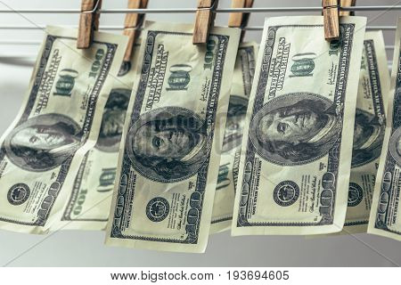 Money laundering. Hundred American dollars hang on clothesline to clean. Financial crime concept