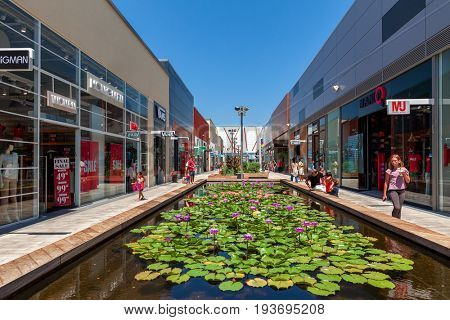 ASHDOD, ISRAEL - JULY 24, 2015: Artificial pond with flowers among shops and boutiques at open air mall - owned by BIG Shopping Centers Ltd, operates in four countries - Israel, USA, India and Serbia.