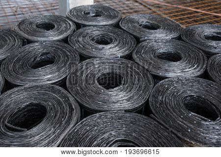 Black bituminous membrane sheet rolls stacked on a palette