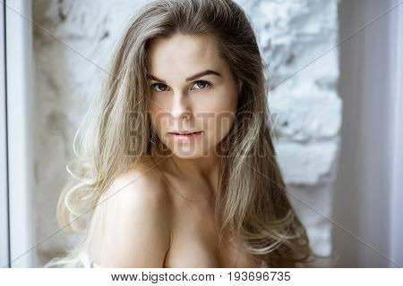 Female portrait of cute lady indoors. Close up beautiful sexy model girl in elegant pose. Closeup beauty blonde woman with hairstyle