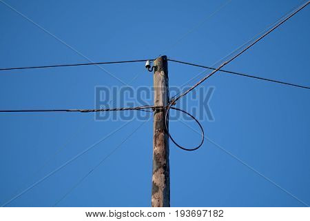 Old low tension electrical pole on blue sky