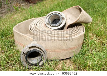 Fire hose for water on green grass