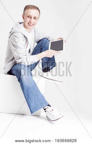 Youth Concepts. Portrait of Smiling Glad Caucasian Man in Hoodie with Tablet Computer Sitting on Studio Box with Leg Lifted. Vertical Image Orientation