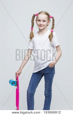 Kids Concepts. Portrait of Little Caucasian Blond Girl with Nice Pigtails Posing With Pink Pennyboard Against White Background. Vertical Image