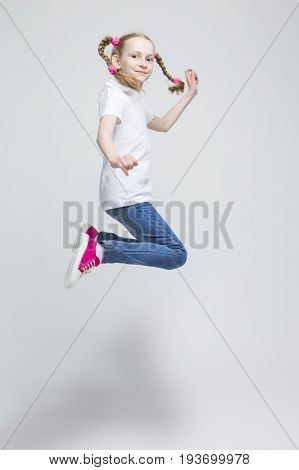 Portrait of Happy Smiling Caucasian Blond Girl With Pigtails Making a High Jump in Studio. Against White Background. Vertical Image Composition