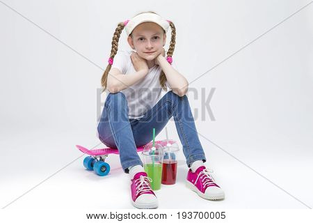 Kids Concepts. Portrait of Little Caucasian Blond Girl in Visor Sitting on Pink Pennyboard With Two Cups of Juice. Against White. Horizontal Image