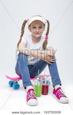 Kids Concepts. Portrait of Little Caucasian Blond Girl in Visor Sitting on Pink Pennyboard With Two Cups of Juice. Against White. Vertical Image