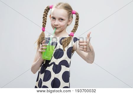 Portrait Of Cute And smiling Caucasian LIttle Girl With Pigtails Posing in Polka Dot Dress with Cup of Greeen Juice. Drinking Through Straw. Showing Thumbs Up Sign. Horizontal Shot