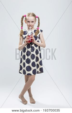 Portrait Of Smiling Caucasian LIttle Girl With Pigtails Standing Barefoot in Polka Dot Dress with Cup of Red Juice. Drinking Through Straw. Vertical Image