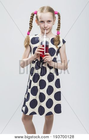 Closeup Portrait of Caucasian Blond Girl With Pigtails Posing in Polka Dot Dress Against White. Holding Cup with Red Juice and Drinking Through Straw.Vertical Image