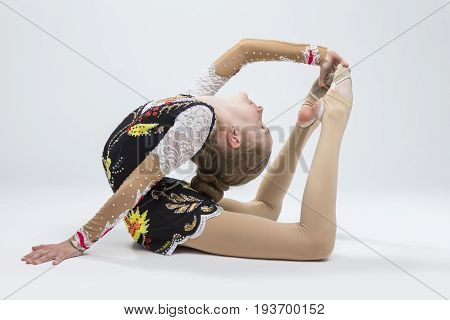 Sport Ideas. Young Caucasian Female Rhythmic Gymnast Athlete In Professional Competitive Suit Doing Backbend Stretching Exercise Pose in Studio Against White.Horizontal Image
