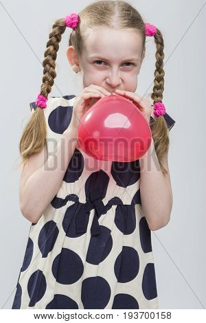 Portrait of Funny Caucasian Blond Girl With Pigtails Posing in Polka Dot Dress Against White. Blowing Up Red Heart Shaped Air Balloon. Vertical Image Composition
