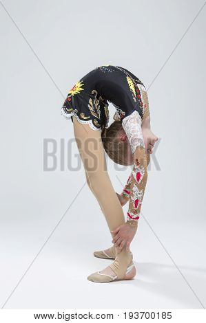 Sport concepts and Ideas. Young Caucasian Female Rhythmic Gymnast Athlete In Professional Competitive Suit Doing Backbend Stretching Exercise While Posing in Studio Against White. Vertical Shot