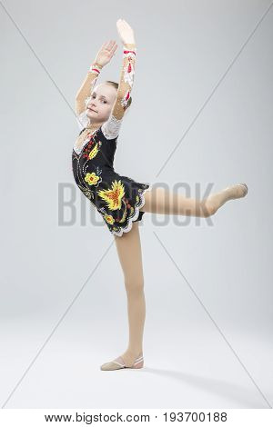 Sport concepts and Ideas. Young Caucasian Female Rhythmic Gymnast Athlete In Professional Competitive Suit Doing Vertical Split Exercise While Posing in Studio Against White. Vertical Shot
