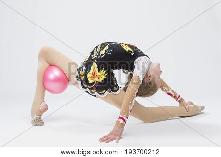 Sport Concepts. Caucasian Female Rhythmic Gymnast Athlete In Professional Competitive Suit Doing Backbend Stretching Exercise With Medium Ball in Studio Against White. Horizontal Image