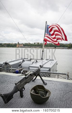 Ship Tour USS Kearsarge (LHD 3) Wasp-class amphibious assault ship: American Flag flies from the bow, with machine gun and helmet on the flight deck. Fleet Week NEW YORK MAY 25 2017.