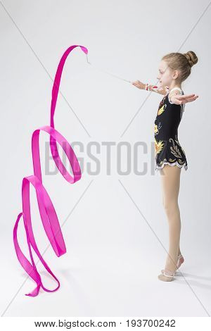 Professional Sport Concepts. Little Caucasian Female Rhythmic Gymnast In Professional Competitive Suit Doing Artistic Ribbon Spirals Exercises in Studio Against White. Vertical Image
