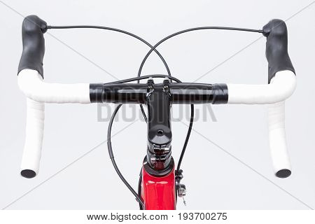 Bicycle Concept. Partial View of Professional Carbon Road Bike Handlebars With White Grip Tape. Against White. Horizontal Image