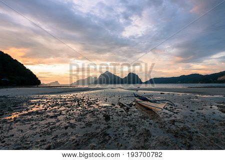 EL NIDO, PALAWAN, PHILIPPINES - MARCH 29, 2017: Lonely boat with spectacular sunset on Palawan Island Las Cabanas Beach.