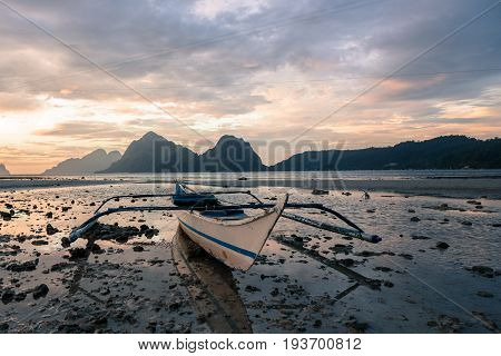 EL NIDO, PALAWAN, PHILIPPINES - MARCH 29, 2017: Low tide with a boat at Las Cabanas Beach.