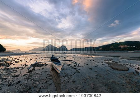 EL NIDO, PALAWAN, PHILIPPINES - MARCH 29, 2017: Horizontal picture of a lonely boat with an amazing sunset at Las Cabanas Beach.