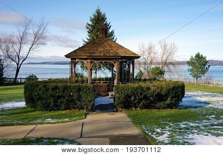 One may sit in a gazebo, in Sunset Park, in Petoskey, Michigan, and enjoy the views of Little Traverse Bay, during November.