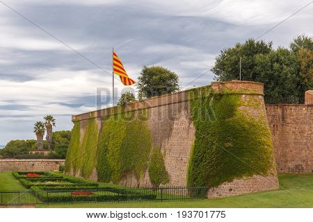 Flag of Catalonia over Montjuic Castle, old military fortress on top of Montjuic hill in Barcelona, Catalonia, Spain