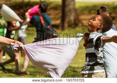 ATLANTA, GA - APRIL 2017: A child avoids being hit by a pillow while taking part in International Pillow Fight Day at Grant Park in Atlanta GA on April 1 2017.
