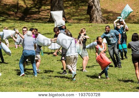 ATLANTA, GA - APRIL 2017:  Several people try to hit each other with pillows on International Pillow Fight Day in Grant Park in Atlanta GA on April 1 2017.