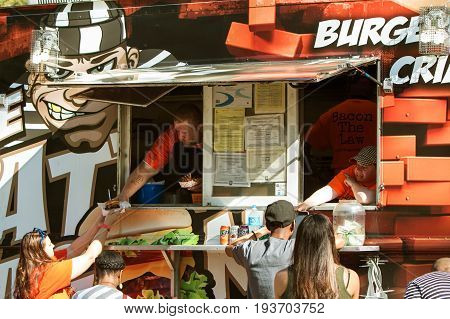 ATLANTA, GA - APRIL 2017:  People get served their food while waiting in line at a food truck at a food truck festival in Grant Park in Atlanta GA, on April 1, 2017 .