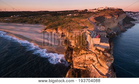 Aerial view of ocean and Nazare lighthouse at sunset Portugal