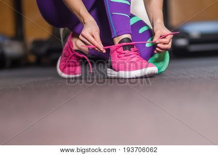 Young woman tying shoelaces in the gym