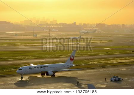 2017 MAY 07, HANEDA INTERNATIONAL AIRPORT TOKYO JAPAN. An airplane of JAL airline prepare to take off to the sky with golden sky in the evening time.