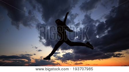 Silhouette of a man against a background of clouds and sunset. He jumps on the roof. Parkour in the evening.