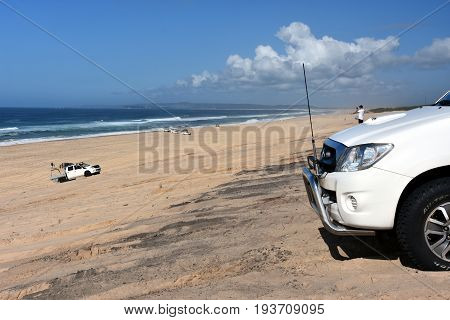 Guys driving 4wd card on the sand dunes. Horizontal landscape of the beach with 4wd cars (Belmont - Nine Miles - Beach NSW Australia). Redhead Point in the background.