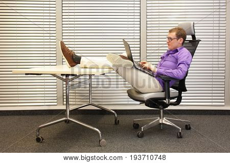 caucasian man working with laptop in relaxed position with legs on desk