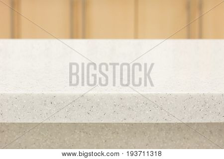 White quartz stone countertop as kitchen island on blurred wooden wall background - can be used for display or montage your products