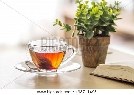 Close up warm black tea cup on the wooden table in living room relax with tea time concept