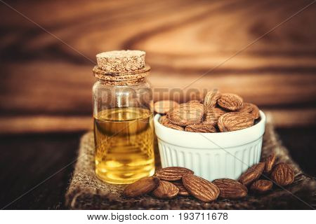 Close up almond oil in the bottle and almond seed in white cup for oil massage and spa treatment ingredient on wooden table background