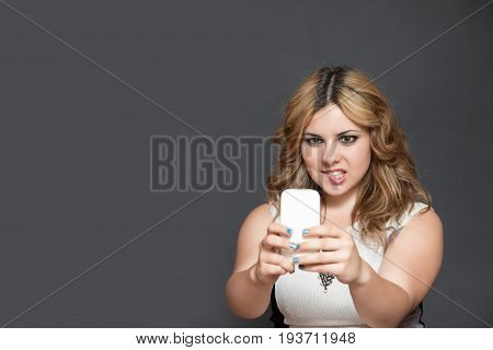 Studio shot of long haired teenage girl biting into her lips is looking at her smart phone.