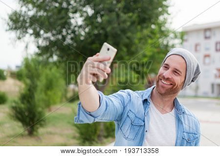 Casual fashion guy taking a photo himself with a mobile in the city