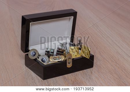 Men's Cufflinks in an open box on a wooden table
